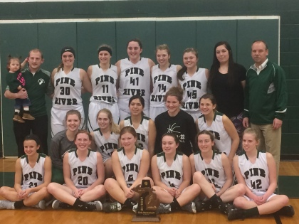 Girls basketball team and coaches in front of trophy.