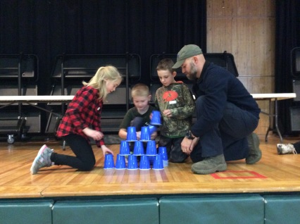 Kids and an adult playing the cup stacking game.