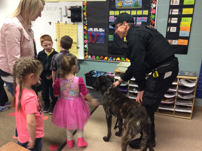 police officer showing dog to students